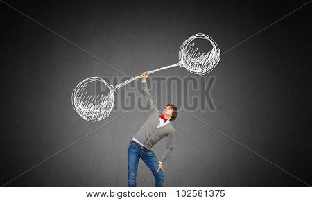 Confident businessman lifting above head barbell with light bulbs