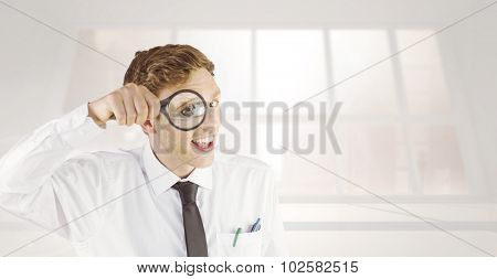 Geeky businessman looking through magnifying glass against bright white room with windows