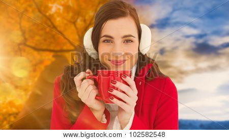 Woman in winter clothes enjoying a hot drink against autumn changing to winter