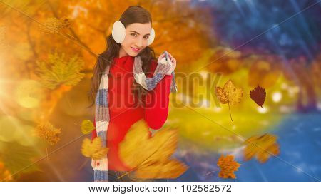 Happy brunette in winter clothes posing against autumn changing to winter