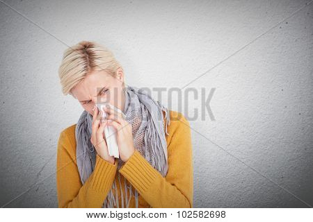 Close up of woman blowing her nose against grey wall