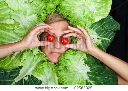 Cute Woman With Salad Leaves Arranged Around Her Head Playing With Tomatoes