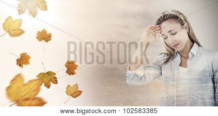 Upset woman touching forehead against autumn leaves pattern