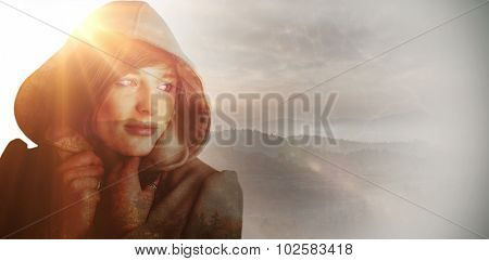 Beautiful woman wearing winter coat looking away against trees and mountain range against cloudy sky