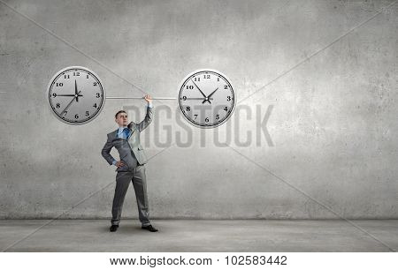 Confident businessman lifting above head barbell with clock