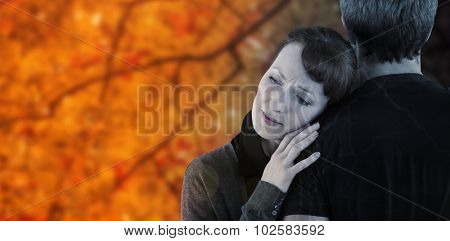 Scared woman holding onto man against autumn scene
