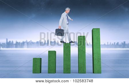 Side view of businessman walking with briefcase over white background against bar chart depicting growth