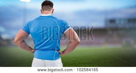 Rugby player with hands on hips against pitch