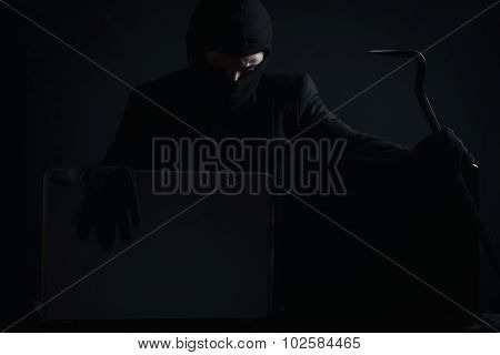 Angry Computer Hacker In Suit Stealing Data From Laptop With Crowbar And Gloves In Front Of Black Ba