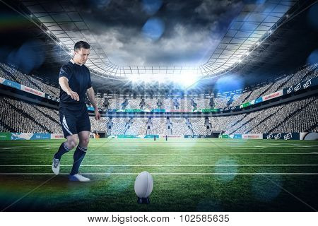 Rugby player doing a drop kick against rugby stadium