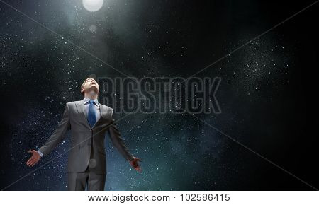 Businessman with hands spread apart on dark background