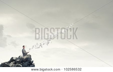Young businessman sitting on rock top with opened book in hand and pages flying in air