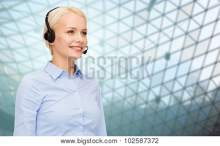 business, people, technology and communication concept - happy female helpline operator in headset over glass grid ceiling background