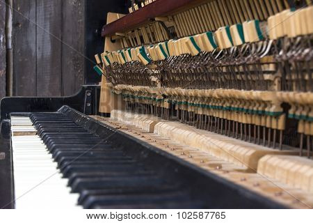 Old piano. Keys and small hammers with selective focus and shallow depth of field.