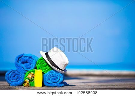 Beach and summer vacation accessories concept - close-up of colorful towels, hat, swimming goggles a