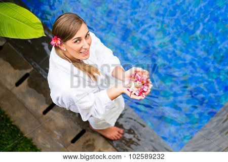 Woman with blossoms wearing bath robe at tropical wellness spa pool