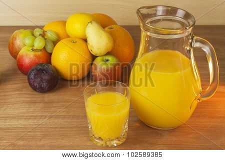 Production of summer fruit juices. Domestic fresh orange juice in a glass jar on a wooden table.