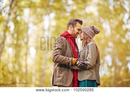 Amorous guy and girl standing face to face in park