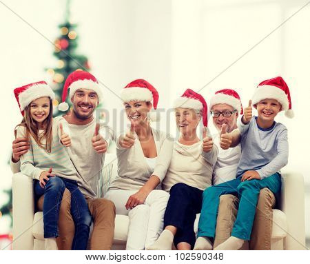 family, home, generation, holidays and people concept - happy family in santa helper hats sitting on couch and showing thumbs up gesture over living room with christmas tree background