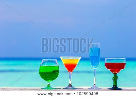 Colorful exotic tasty cocktails in outdoor cafe background turquoise sea at exotic resort