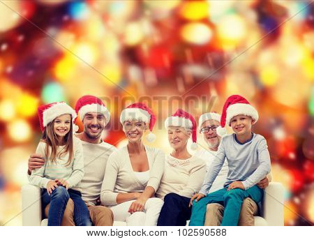 family, happiness, generation, holidays and people concept - happy family in santa helper hats sitting on couch over red lights background
