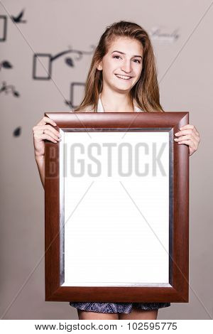 Happy young girl holding portrait frame