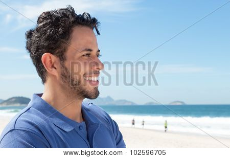 Guy with beard and blue shirt at beach looking sideways