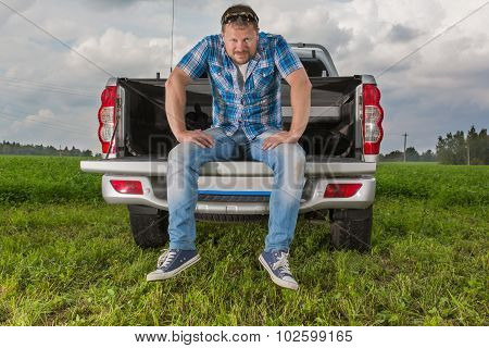 Solid man sitting on car trunk