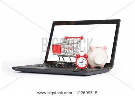 Shopping cart, clock and piggy bank on laptop