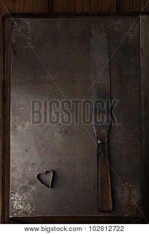 Vintage  Baking utensils - spatula and heart shape cutter on dark metal backdrop