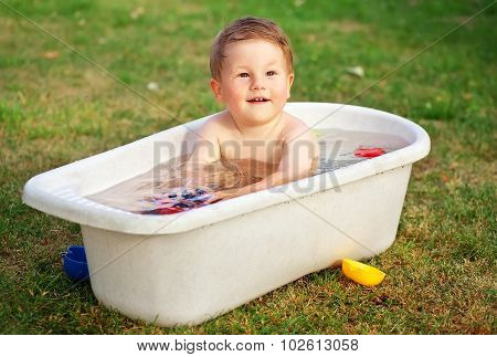 A Small Happy Baby Bathed In The Bath And Playing In A Bath With Toys.
