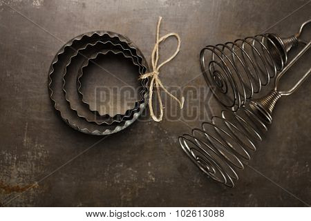 Vintage  Baking Tin cutters and whisk, in dark light