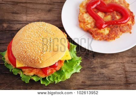 Hamburger And Chicken Cutlet On A Old Wooden Table.