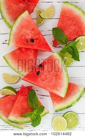 Slices of ripe juicy organic watermelon on a wooden background served with fresh lime and mint leave