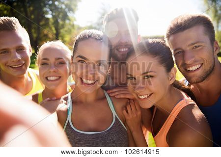 fitness, sport, friendship, technology and healthy lifestyle concept - group of happy teenage friends taking selfie with smartphone outdoors