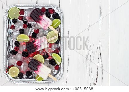 Berry vanilla ice pops - popsicles - in a vintage silver ice tray over old rustic wooden background