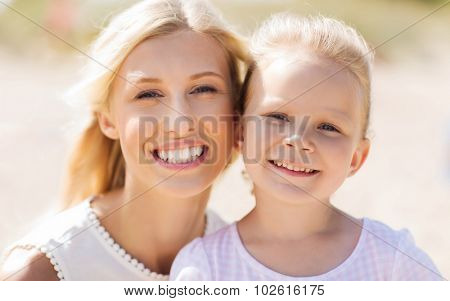 family, travel, vacation, adoption and people concept - happy mother and little daughter on summer beach