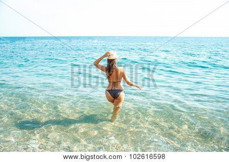 Woman In Sun Hat And Bikini Standing With Her Arm Raised To Her Head Enjoying Looking View Of Beach