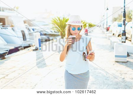 Happy Young Woman Drinking Takeaway Coffee And Walking On The Waterfront In The Morning