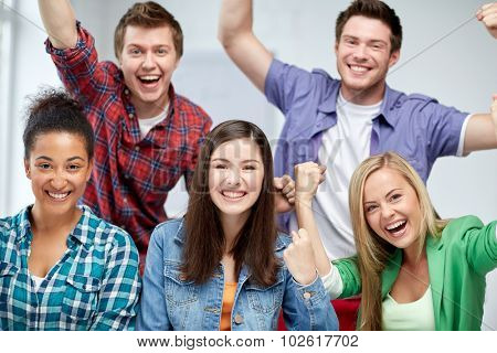 education, people, friendship and learning concept - group of happy international high school students making triumph gesture or classmates