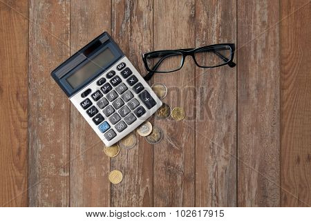 busines, finance, money and bookkeeping concept - calculator, eyeglasses and euro coins on wooden table background