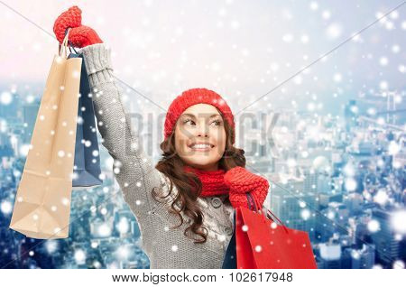 holidays, christmas, x-mas, sale and people concept - happy young asian woman in winter clothes with shopping bags over snow and city background