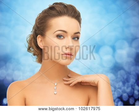 people, jewelry, luxury and glamour concept - woman wearing shiny diamond pendant over blue lights background