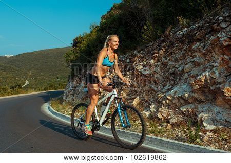 Woman Riding A Bike On A Mountain Road
