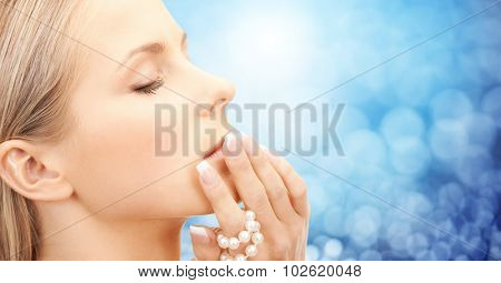 beauty, luxury, people, holidays and jewelry concept - face of beautiful woman with sea pearl beads in hand over blue lights background