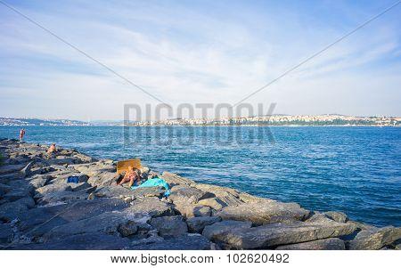 Man Sleeping On Rocks At Bosphorus Bank