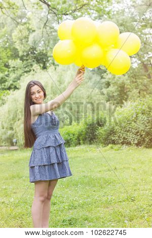 Happy Young Woman With Yellow Balloons