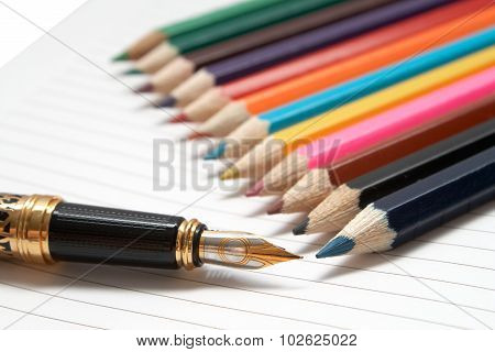 Office tools. Golden Pen and colored wooden pencils