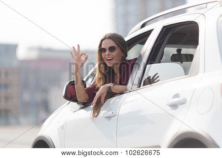 Beautiful lady showing okay sign from her car