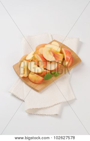 apple slice on wooden cutting board and white place mat